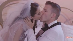 Bride in a wedding dress and the groom in a tuxedo make love